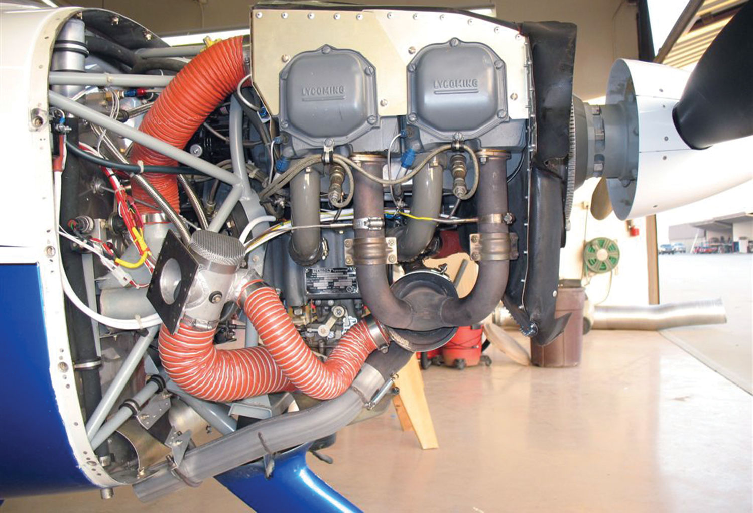 The original Sportsman exhaust system is similar to that on a Cessna—a large can-type muffler tucked underneath the engine and a single exhaust pipe leading out of the cowl.