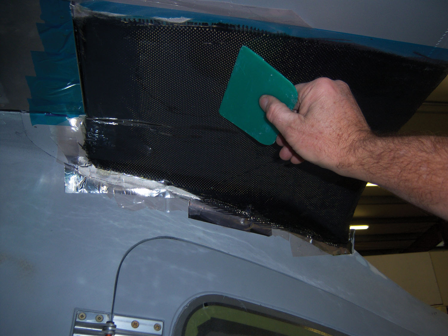 Using a squeegee to get any air bubbles and wrinkles out of the laminate The bagging film seals the laminate and keeps the whole process from getting messy.