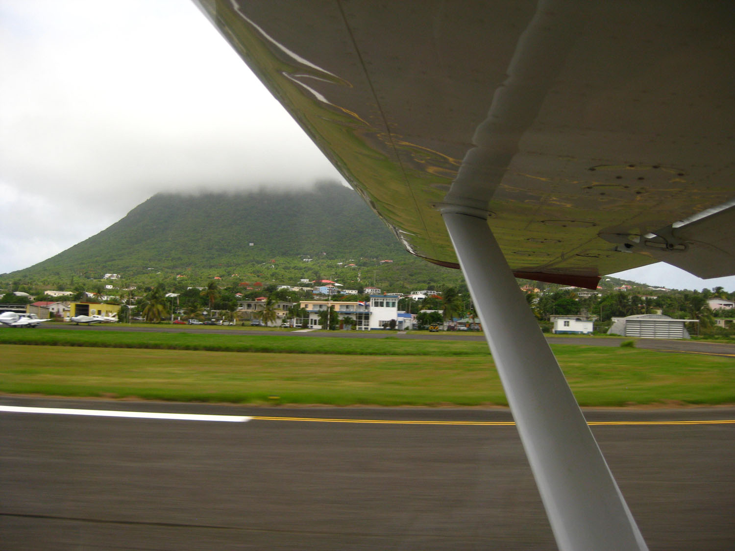 "St. Eustatius Internatioal apt. off the right wingtip with ""the Quill"" in the background"