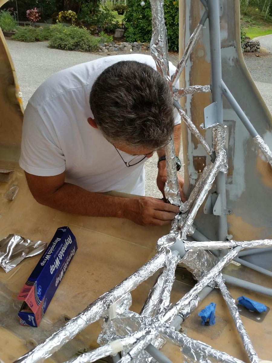Craig Gillson covering the cage in order to spray the grey primer and Zolatone.