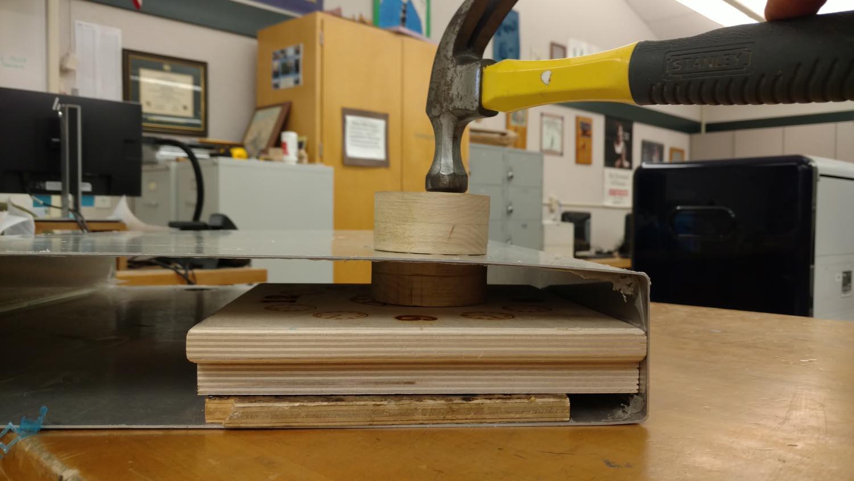 Sandwiching metal between homemade dies to create dimple for fuel drain.
